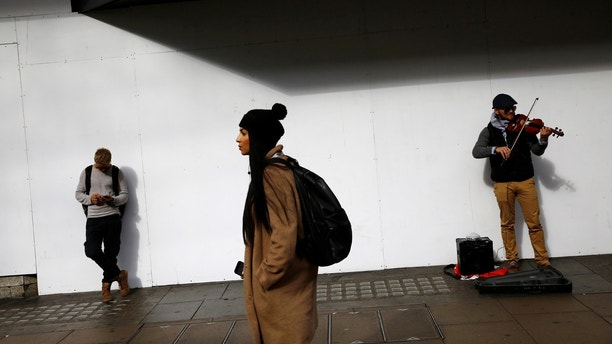 """A man looks at his mobile phone next to a busker in Oxford Street, London, Britain October 6, 2016. REUTERS/Stefan Wermuth SEARCH """"WERMUTH PHONES"""" FOR THIS STORY. SEARCH """"THE WIDER IMAGE"""" FOR ALL STORIES. - RC1901A007C0"""