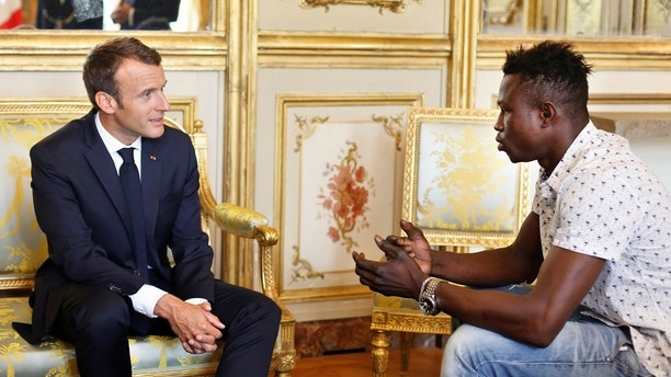 French President Emmanuel Macron (L) meets with Mamoudou Gassama, 22, from Mali, at the Elysee Palace in Paris, France, May 28, 2018. Mamoudou Gassama living illegally in France is being honored by Macron for scaling an apartment building over the weekend to save a 4-year-old child dangling from a fifth-floor balcony. Thibault Camus/Pool via Reuters - RC1CBB2EE560