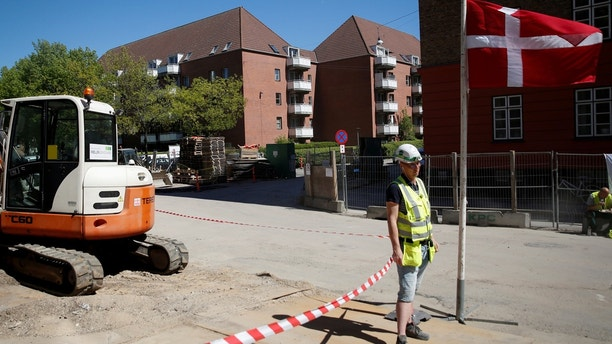A worker stands beside a Danish flag on a construction site of new housing being built next to Mjolnerparken, a housing estate that features on the Danish government's  Denmark to force 'ghetto' children to learn about democracy, Christmas Denmark to force 'ghetto' children to learn about democracy, Christmas 1527598298759