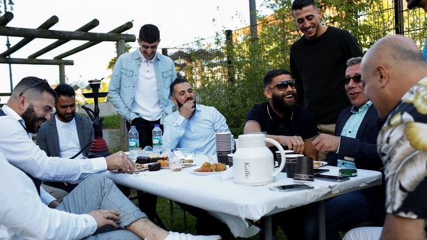 "Guests from places within Denmark and Northern Europe sit together at the engagement party of a resident in Mjolnerparken, a housing estate that features on the Danish government's ""Ghetto List"", in Copenhagen, Denmark, May 6, 2018. REUTERS/Andrew Kelly     SEARCH ""DENMARK GHETTO"" FOR THIS STORY. SEARCH ""WIDER IMAGE"" FOR ALL STORIES. THE IMAGES SHOULD ONLY BE USED TOGETHER WITH THE STORY - NO STAND-ALONE USES. TPX IMAGES OF THE DAY - RC11F9055400"