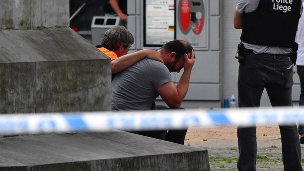 A police man stands next to a man who holds his head in his hands at the scene of a shooting in Liege, Belgium, Tuesday, May 29, 2018. A gunman killed three people, including two police officers, in the Belgian city of Liege on Tuesday, a city official said. Police later killed the attacker, and other officers were wounded in the shooting.(AP Photo/Geert Vanden Wijngaert)