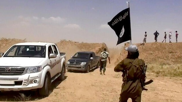 This image posted on a militant news Twitter account on Thursday, June 12, 2014 shows militants from the al-Qaida-inspired Islamic State of Iraq and the Levant (ISIL)  removing part of the soil barrier on the Iraq-Syria borders and moving through it. Fresh gains by insurgents, spearheaded by fighters from the al-Qaida-inspired Islamic State of Iraq and the Levant, come as Prime Minister Nouri al-Maliki's Shiite-led government struggles to form a coherent response after militants overran the country's second-largest city of Mosul, Saddam Hussein's hometown of Tikrit and smaller communities, as well as military and police bases — often after meeting little resistance from state security forces.(AP Photo/albaraka_news)