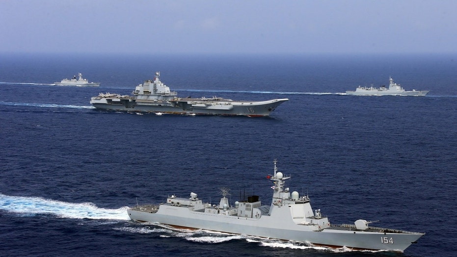 China's aircraft carrier Liaoning (C) takes part in a military drill of Chinese People's Liberation Army (PLA) Navy in the western Pacific Ocean, April 18, 2018.