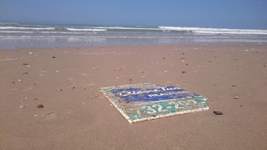 Realty sign lost during Superstorm Sandy ends up on French beach