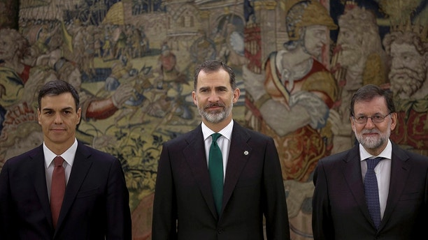 Spain's socialist leader Pedro Sanchez, left, poses with King Felipe VI, center and former Prime Minister Mariano Rajoy after the swearing in ceremony at the Zarzuela Palace on the outskirts of Madrid, Spain, Saturday June 2, 2018. Pedro Sanchez has been sworn in as Spain's Prime Minister by King Felipe VI in a ceremony after coming to power Saturday a day after successfully leading a no-confidence vote to oust conservative Prime Minister Mariano Rajoy. (Emilio Naranjo/Pool Photo via AP)