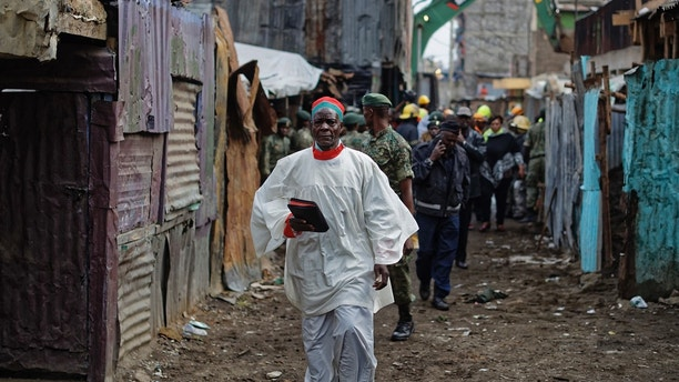 A priest holding a bible walks past the scene of a five-storey collapsed building in the Huruma neighborhood of Nairobi, Kenya Sunday, June 3, 2018. An official from Kenya's Disaster Management Unit at the scene said that two had died, a number were injured, some were still missing, but that many residents of the building had managed to escape before the building fully collapsed. (AP Photo/Ben Curtis)