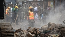 A rescuer aided by a heavy digger attends the scene of a five-storey collapsed building in the Huruma neighborhood of Nairobi, Kenya Sunday, June 3, 2018. An official from Kenya's Disaster Management Unit at the scene said that two had died, a number were injured, some were still missing, but that many residents of the building had managed to escape before the building fully collapsed. (AP Photo/Ben Curtis)
