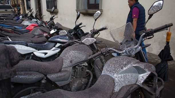 Volcanic ash covers parked motorcycles, brought by the Fuego Volcano, in Antigua Guatemala, Sunday, June 3, 2018. Volcan del Fuego is one of the most active volcanoes in Central America. (AP Photo/Luis Soto)