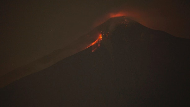 In this image taken with a long exposure, the Volcan de Fuego, or Volcano of Fire, spews hot molten rock from its crater in Alotenango, Guatemala, Sunday, June 3, 2018. Rescuers struggled to reach rural residents cut off by the deadly volcanic eruption Sunday. (AP Photo/Luis Soto)