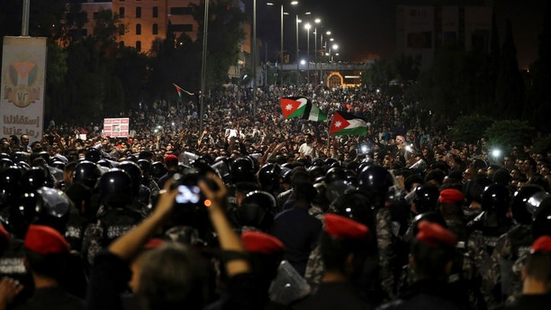 Jordanian protesters shout slogans and raise a national flag during a demonstration outside the Prime Minister's office in the capital Amman late early Monday,  June 4, 2018. Thousands of Jordanians protested against a planned tax increase for a fourth straight day Sunday, marching toward the office of the prime minister and demanding his resignation.(AP Photo/Raad Adayleh)