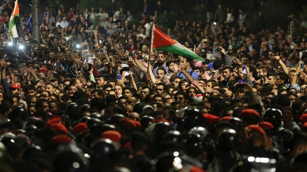 Jordanian protesters shout slogans and raise a national flag during a demonstration outside the Prime Minister's office in the capital Amman early Monday, June 4, 2018. Thousands of Jordanians protested against a planned tax increase for a fourth straight day Sunday, marching toward the office of the prime minister and demanding his resignation. (AP Photo/Raad Adayleh)