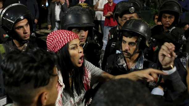 Jordanian protesters argue with members of the gendarmerie and security forces during a demonstration outside the Prime Minister's office in the capital Amman early Monday, June 4, 2018.  Thousands of Jordanians protested against a planned tax increase for a fourth straight day Sunday, marching toward the office of the prime minister and demanding his resignation.(AP Photo/Raad Adayleh)