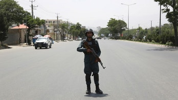 A member of security personnel stands at the site of a deadly suicide attack in Kabul, Afghanistan, Monday, June 4, 2018. A suicide bombing targeted a gathering of Afghanistan's top clerics on Monday in Kabul, killing at least seven people and wounding nine. (AP Photo/Rahmat Gul)