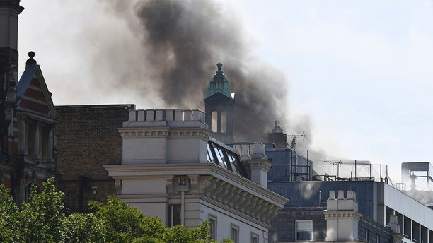 Smoke rises from a building in Knightsbridge, central London, as London Fire Brigade responded to a call of a fire in this upmarket location, Wednesday June 6, 2018. (John Stillwell/PA via AP)