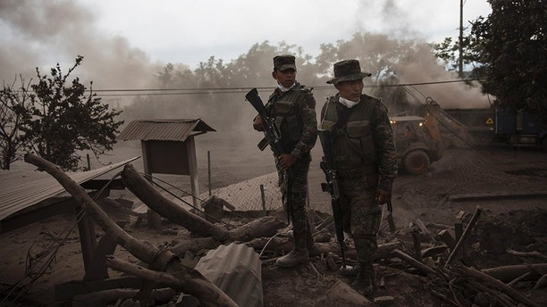 "Soldiers stand guard outside a destroyed home in the disaster zone covered in volcanic ash near the Volcan de Fuego, or ""Volcano of Fire, in the El Rodeo hamlet of Escuintla, Guatemala, Wednesday, June 6, 2018. Firefighters said the chance of finding anyone alive amid the still-steaming terrain was practically nonexistent 72 hours after Sunday's volcanic explosion. (AP Photo/Rodrigo Abd)"