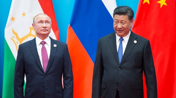 Chinese President Xi Jinping, right, and Russian President Vladimir Putin pose for a photo at the Shanghai Cooperation Organization (SCO) Summit in Qingdao in eastern China's Shandong Province Sunday, June 10, 2018. (AP Photo/Alexander Zemlianichenko)