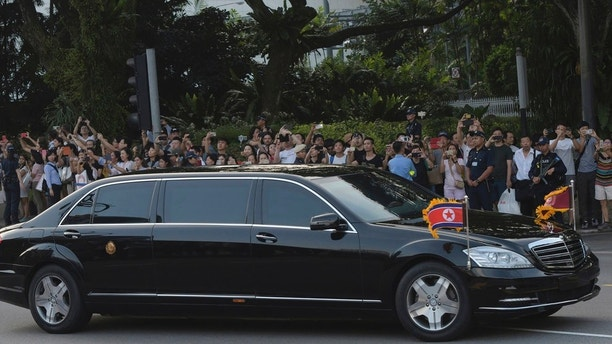 A crowd looks on as the limousine believed to be carrying North Korea leader Kim Jong Un arrives at the Istana, or Presidential Palace, in Singapore on Sunday, June 10, 2018, to meet Singapore Prime Minister Lee Hsien Loong. (AP Photo/Joseph Nair)
