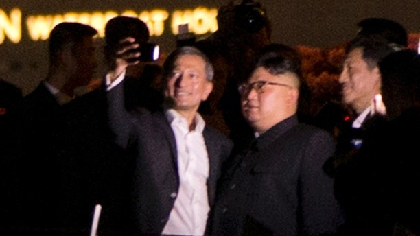 Vivian Balakrishnan, left, Foreign Minister of Singapore takes a selfie with North Korean leader Kim Jong Un walks in Marina Bay, Singapore Monday, June 11, 2018 ahead of the summit with U.S. President Donald Trump. On the eve of their unprecedented summit, President Donald Trump and North Korean leader Kim Jong Un prepared Tuesday for a meeting that could define the fate of millions, along with their own political futures. (AP Photo/Gemunu Amarasinghe)