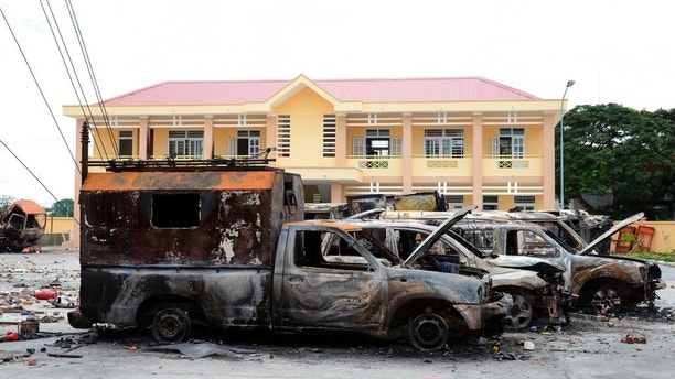 In this photo taken on Tuesday June 12, 2018, a row of charred vehicles is seen at the fire and police station in the south central province of Binh Thuan, Vietnam. Vietnamese protesters clashed with police on Sunday and Monday in the province to protest over a proposed law on special economic zones they fear will be dominated by Chinese investors. The National Assembly on Monday voted to put on hold the legislation for several months. State media reported that police in the south central province of Binh Thuan on Sunday night used tear gas and water cannons but failed to prevent protesters from entering a government building they later vandalized. (AP Photo)