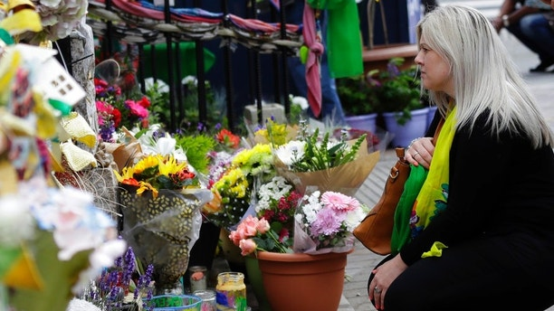 A woman looks at tributes outside Notting Hill Methodist Church in support for those affected by the massive fire in Grenfell Tower in London, Thursday, June 14, 2018. A year ago, London's Grenfell Tower high-rise was destroyed by a fire that killed 72 people. It was Britain's greatest loss of life by fire since World War II. On Thursday survivors, bereaved families and people around Britain will mark the anniversary of a local tragedy that's also a national shame - one for which blame is still being traded. (AP Photo/Kirsty Wigglesworth)