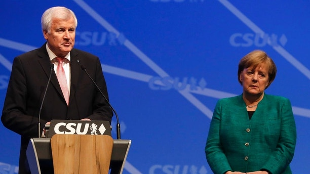 FILE - In this Dec. 15, 2017 photo German Chancellor and chairwoman of the Christian Democratic Union (CDU) party, Angela Merkel, stands besides Bavarian State Governor and Chairman of German Christian Social Union party, CSU, Horst Seehofer, at a party convention of the German Christian Social Union, CSU, in Nuremberg, Germany. (AP Photo/Matthias Schrader)