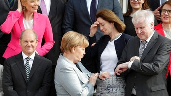 FILE - In this April 10, 2018 file photo German Chancellor Angela Merkel, front center, and German Interior Minister Horst Seehofer, right, look at their watches after they and other members of the government posed for a group photo during two-day retreat at the government guest house Meseberg castle in Gransee north of Berlin, Germany. (AP Photo/Michael Sohn, file)