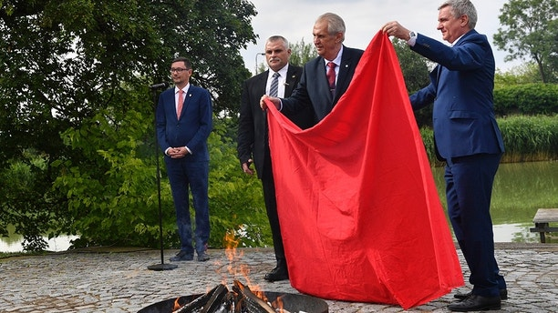 "Czech President Milos Zeman (2nd from right) burns the red trunks, which the Ztohoven artistic group hanged out at the Prague Castle's roof instead of the presidential flag in 2015, in the Castle garden with journalists present on Thursday, June 14, 2018. On this occasion, Zeman told reporters that politics should be done on the basis of the exchange of arguments and not based on underwear. He added that the times of underwear in politics were over. ""To demonstrate this opinion, I have decided to burn the red trunks we bought from the Office for the Government Representation in Property Affairs for a single crown,"" Zeman said. The Castle firefighters in their full professional outfits then laid the red boxer shorts on the fireplace and burnt them near a pond in the Lumbe Garden in the Castle complex. The Presidential Office announced on Wednesday that Zeman would give a press briefing at 16:30 on Thursday, but Zeman's spokesman Jiri Ovcacek kept the issue of the briefing secret. This provoked the media and public speculations. Zeman told reporters that he had tested their intelligence in vain. ""I am sorry to make blockheads of you, you really do not deserve this,"" he told dozens of journalists. On the photo with Zeman are seen Zeman""s spokesman Jiri Ovcacek (left) and Presidenatil office head Vratislav Mynar (right). Photo/Michal Kamaryt (CTK via AP Images)"