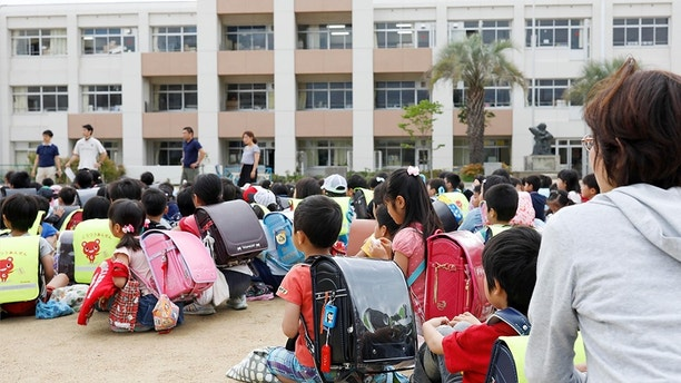 School children take shelter at schoolyard in Ikeda, Osaka, following an earthquake Monday, June 18, 2018.  A strong earthquake has shaken the city of Osaka in western Japan. There are reports of scattered damage including broken glass and concrete. (Takaki Yajima/Kyodo News via AP)