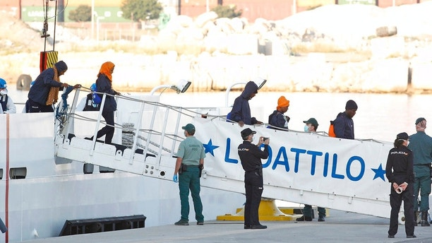 Migrants descend the Italian coast guard vessel Dattilo upon arrival at the eastern port of Valencia, Spain, Sunday, Jun. 17, 2018. The first Italian government ship accompanying the migrant aid vessel Aquarius with 630 people aboard on Sunday docked at the Spanish port ending a weeklong perilous crossing of the Mediterranean. (AP Photo/Alberto Saiz)