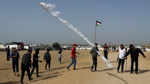 Palestinians set a kite on fire, to be thrown at the Israeli side during clashes at the Israel-Gaza border in the central Gaza strip, April 18, 2018. REUTERS/Ibraheem Abu Mustafa - RC1782291260