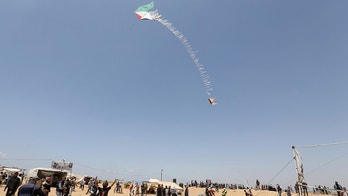 Palestinian demonstrators fly a flaming kite to be thrown at the Israeli side during a protest demanding the right to return to their homeland, at the Israel-Gaza border in the southern Gaza Strip, May 11, 2018. REUTERS/Ibraheem Abu Mustafa - RC13D60EFAD0