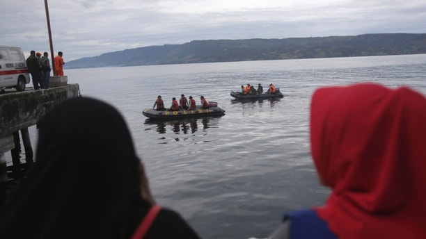 Indonesian search and rescue team on boat searches for a ferry which sank Monday at Tigaras port in Toba lake, North Sumatra, Wednesday, June, 20, 2018. Distraught relatives slammed Indonesia's government for not enforcing basic safety measures on passenger boats and pleaded Wednesday for a bigger search effort for the people missing since a ferry sank on a picturesque Sumatran lake early this week.(AP Photo/Binsar Bakkara)