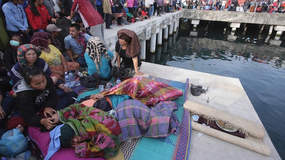 Relatives of victims of a sunken ferry wait for news at the Tigaras port in Toba lake, North Sumatra, Wednesday, June, 20, 2018.