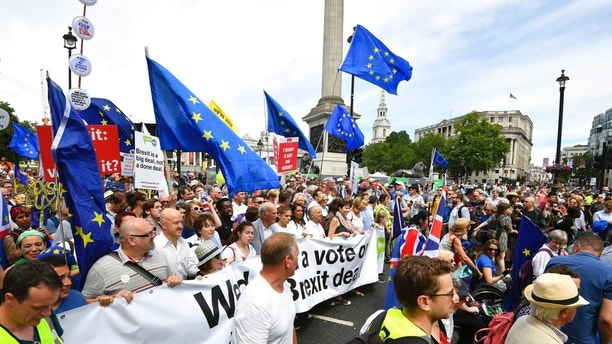 From centre carrying banner, British lawmaker Vince Cable,  Pro-EU campaigners Gina Miller, Tony Robinson and lawmaker Caroline Lucas join crowds taking part in the People's Vote march for a second EU referendum, at Trafalgar Square in central London,  Saturday June 23, 2018. Leading Brexit supporters are talking tough, and opponents are taking to the streets, on the second anniversary of Britain's vote to leave the European Union. Saturday marks two years since a June 23, 2016 referendum resulted in a decision to quit the 28-nation EU. (John Stillwell/PA via AP)