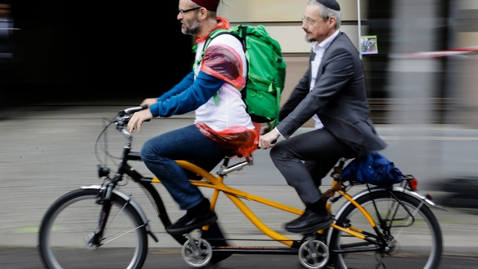 A Muslim and a Jewish man rides a tandem together during a bicycle tandem tour of Jews and Moslems against anti-Semitism and hatred of Muslims in Berlin, Sunday, June 24, 2018. (AP Photo/Markus Schreiber)