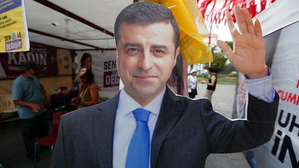 FILE - In this Wednesday, June 20, 2018 file photo, a cardboard cut-out of Selahattin Demirtas, the jailed former co-chair and the presidential candidate of the pro-Kurdish Peoples' Democratic Party, (HDP), who is fighting terrorism-related charges, is pictured at an election kiosk in Istanbul.Demirtas is in prison in Edirne, Turkey from where he is running his election campaign. Turkish voters are heading to the polls June 24 to vote in crucial presidential and parliamentary elections that could either solidify President Recep Tayyip Erdogan's grip on power or unsettle his political ambitions. (AP Photo/Lefteris Pitarakis, File)