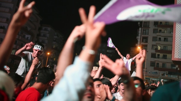 Supporters of the pro-Kurdish Peoples' Democratic Party, or HDP, celebrate in the mainly-Kurdish city of Diyarbakir, southeastern Turkey, Sunday, June 24, 2018. Partial results show the pro-Kurdish party has passed a critical electoral threshold to enter the Turkish parliament, risking the ruling party's majority. (AP Photo/Emre Tazegul)