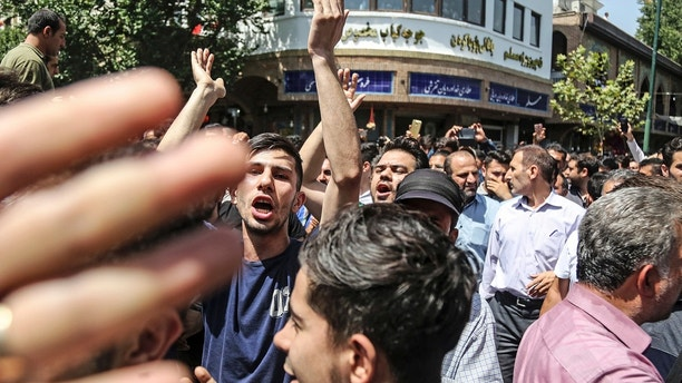 A group of protesters chant slogans at the main gate of old grand bazaar in Tehran, Iran, Monday, June 25, 2018. Protesters in the Iranian capital swarmed its historic Grand Bazaar on Monday, news agencies reported, and forced shopkeepers to close their stalls in apparent anger over the Islamic Republic's troubled economy, months after similar demonstrations rocked the country. (Iranian Labor News Agency via AP)  Protesters swarm Iran's Grand Bazaar in Tehran, force shops to close in anger over economy 1529937250788