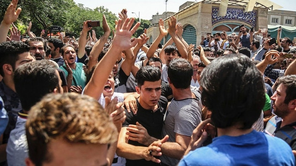 A group of protesters chant slogans at the main gate of old grand bazaar in Tehran, Iran, Monday, June 25, 2018. Protesters in the Iranian capital swarmed its historic Grand Bazaar on Monday, news agencies reported, and forced shopkeepers to close their stalls in apparent anger over the Islamic Republic's troubled economy, months after similar demonstrations rocked the country. (Iranian Labor News Agency via AP)  Protesters swarm Iran's Grand Bazaar in Tehran, force shops to close in anger over economy 1529937232655