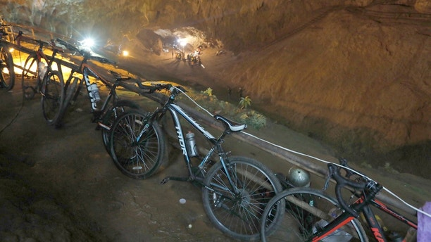 Bicycles left by a group of missing boys lean against a railing at the entrance of a deep cave in Chiang Rai, northern Thailand, Monday, June 25, 2018. Officials say multiple attempts to locate the 12 boys and their soccer coach missing in a flooded cave in northern Thailand for nearly two days have failed, but that they will keep trying. (Thai News Pix via AP)