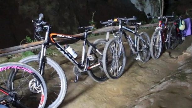 In this image made from video taken Sunday, June 24, 2018, bicycles left from a group of boys who went missing stand parked outside a deep cave in Chang Rai, northern Thailand. Officials say multiple attempts to locate the 12 boys and their soccer coach missing in a flooded cave in northern Thailand for nearly two days have failed, but that they will keep trying. (TPBS via AP)