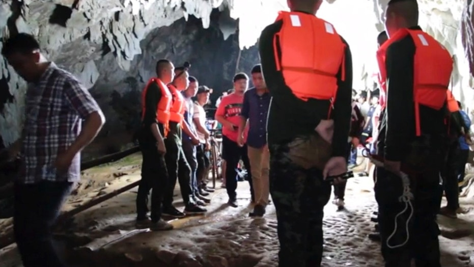 In this image made from video taken Sunday, June 24, 2018, rescue teams gather at the entrance of a deep cave where a group of boys went missing in Chang Rai, northern Thailand.
