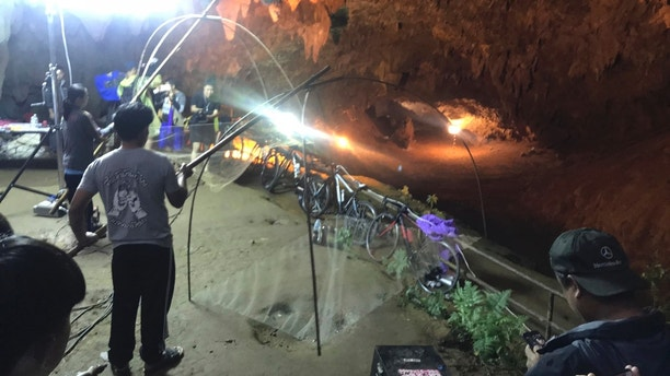 Relatives hold fishing nets, as a symbol to fish out lost spirits inside cave, as a group of locals and relatives perform a ritual calling for those are missing at the entrance of the cave, Tuesday, June 26, 2018, in Mae Sai, Chiang Rai province, northern Thailand. Electricians are extending a power line into a flooded cave in northern Thailand to help the search and rescue efforts for 12 boys and their soccer coach stranded three nights in the sprawling caverns and cut off by rising water. (AP Photo/Tassanee Vejpongsa)  Search for youth soccer team trapped in Thailand cave complicated by more flooding 1530011915800