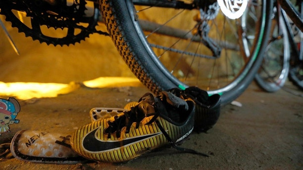 A pair of soccer shoes are left next to bicycles from a group of missing boys at the entrance of a deep cave in Chiang Rai, northern Thailand, Monday, June 25, 2018. Officials say multiple attempts to locate the 12 boys and their soccer coach missing in a flooded cave in northern Thailand for nearly two days have failed, but that they will keep trying. (Thai News Pix via AP)
