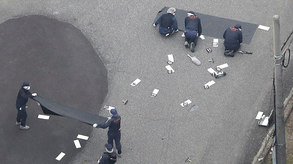June 26, 2018: Investigators work at an elementary school after a man fatally shot a security guard, in Toyama, northwest of Tokyo.