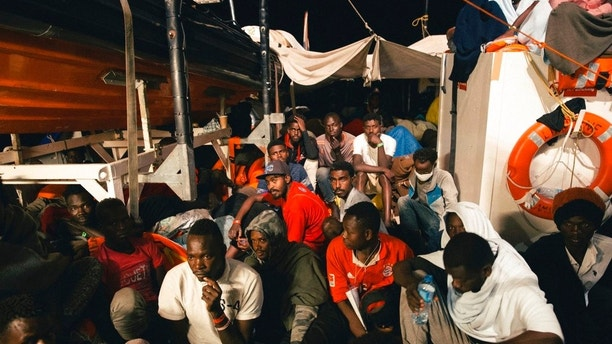 Rescued migrants sit in the search and rescue ship of German aid group Mission Lifeline as the boat remained stranded off Malta with 234 migrants aboard and no port at which to dock after both Italy and Malta refused to give authorization, early Monday, June 25, 2018. Since taking office at the beginning of the month, Italian Interior Minister Matteo Salvini has launched a crackdown on private European-flagged rescue ships. (Mission Lifeline via AP)