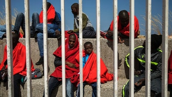 Migrants rest at the port of Algeciras, southern Spain, as they wait to be transported to a police station after being rescued in the Strait of Gibraltar, Tuesday, Jun. 26, 2018. Spain's Maritime Rescue Service says it has picked up just over 400 people from the Mediterranean as migrants hasten to reach Spain from North Africa while the weather remains fair. (AP Photo/Emilio Morenatti)