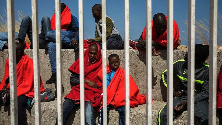 Migrants resting at the port of Algeciras, southern Spain, as they waited to be transported to a police station after being rescued in the Strait of Gibraltar on Tuesday.  Aid ship docks in Malta with 234 refugees, ending extended journey 1530132656758