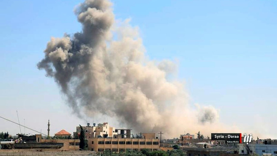 This Tuesday, June 26, 2018 photo provided by Nabaa Media, a Syrian opposition media outlet, shows smoke rising over buildings that were hit by Syrian government forces bombardment, in Daraa, southern Syria.