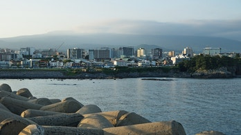 Cityscape with wavebreakers of Seogwipo with mount Hallasan in background, Jeju Island, South Korea